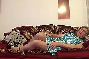 Transvestite lounges on Sofa in Green Dress -  Johanna Clayton